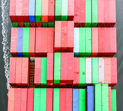 Multicolored sea containers, laid flat with stacks for storage and transportation